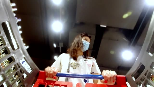 Woman, wearing disposable medical mask and shopping in supermarket during coronavirus pneumonia outbreak. Protection and prevent measures while epidemic time - vídeo
