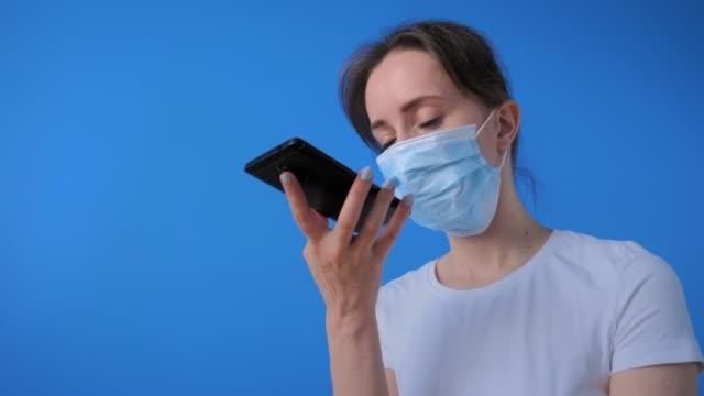 frau trägt gesichtsmaske, hält smartphone, mit spracherkennungsfunktion - smartphone mit corona app stock-videos und b-roll-filmmaterial