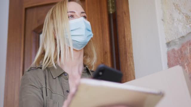 donna che indossa la maschera facciale che effettua il pagamento al fattorino attraverso il suo telefono - grocery home video stock e b–roll