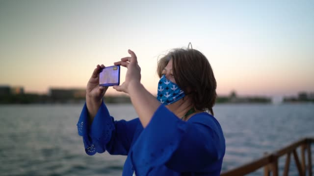 Woman wearing face mask taking photographing or filming sunset