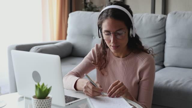 vidéos et rushes de femme utilisant la conférence d'apprentissage à distance d'écouteurs - professeur(e)
