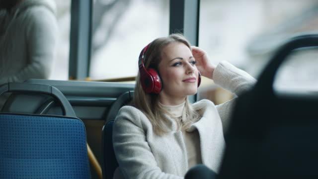 otobüste kafasına kulaklık takan kadın - kulaklık seti ses ekipmanı stok videoları ve detay görüntü çekimi