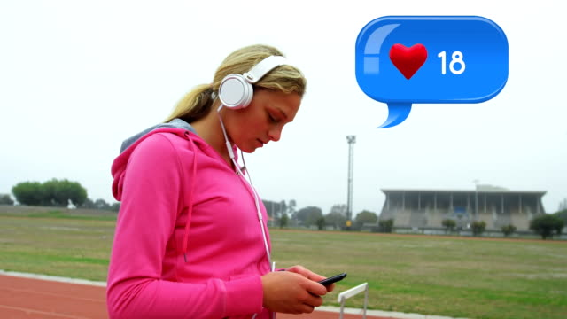 Woman wearing headphones while texting Side view of a Caucasian woman wearing a headset texting at a track and field. Beside her in the foreground is a digital animation of a message bubble with a heart icon increasing in count telephone receiver stock videos & royalty-free footage