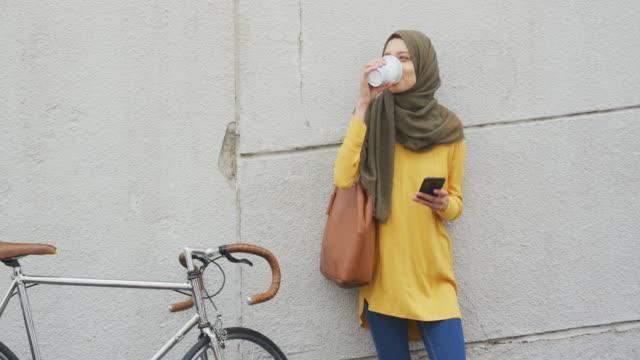Woman wearing hijab drinking in the street with a take away coffee