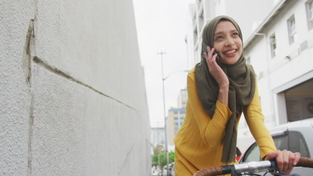 Woman wearing hijab having a phonecall on a bike