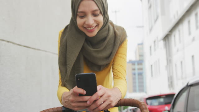 Woman wearing hijab using her phone on a bike