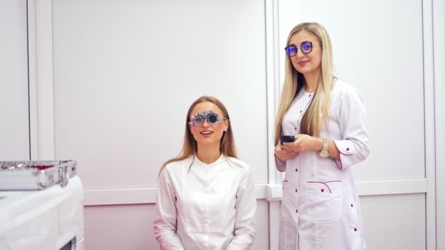 vidéos et rushes de femme utilisant dans l'équipement d'ophtalmologie - réfracteur