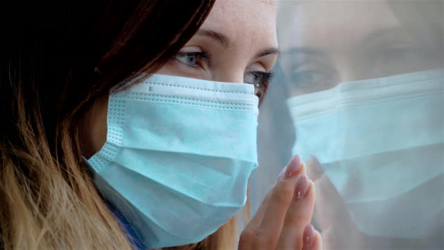 Kvinna bär mask och tittar på fönster för sjukvård och medicinskt koncept video