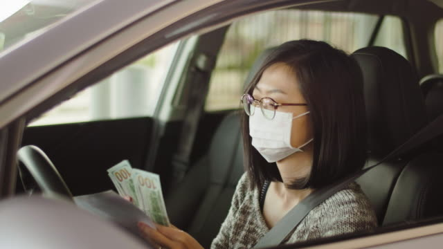 woman wearing mask at drive-through bank - banks and atms stock videos & royalty-free footage