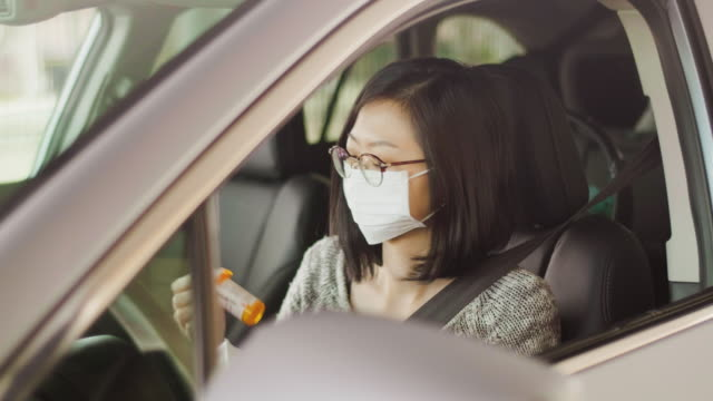 Woman Wearing Mask at Drive-Through Pharmacy A woman wearing a mask, picking up medicine from a drive-through pharmacy. prescription stock videos & royalty-free footage