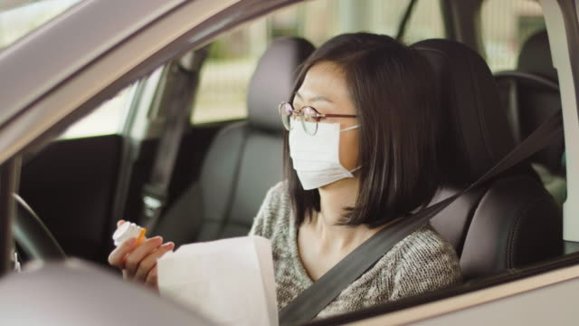 Woman Wearing Mask at Drive-Through Pharmacy A woman wearing a mask, picking up medicine from a drive-through pharmacy. pharmacy stock videos & royalty-free footage