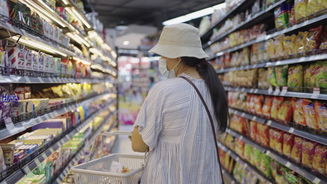 Woman wearing mask buying snack in store Close shot of young woman wearing mask buying snack in store during coronavirus epidemic snack aisle stock videos & royalty-free footage