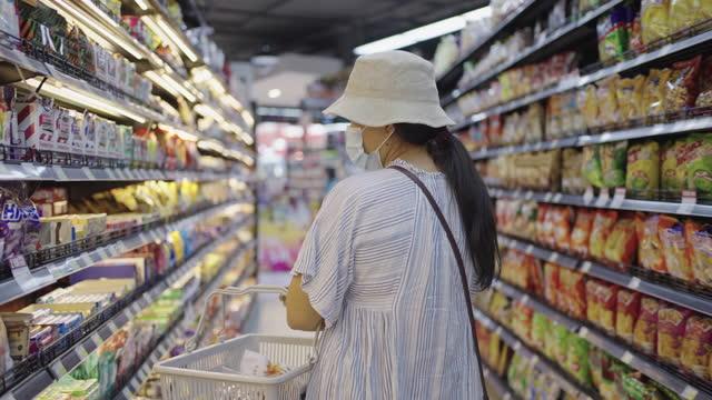 vídeos y material grabado en eventos de stock de mujer usando máscara comprando merienda en la tienda - snack aisle