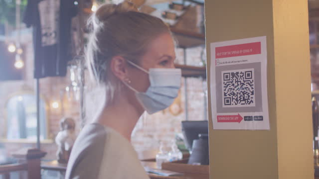 Woman wearing mask with mobile phone checking into venue scanning QR code during health pandemic - shot in slow motion video