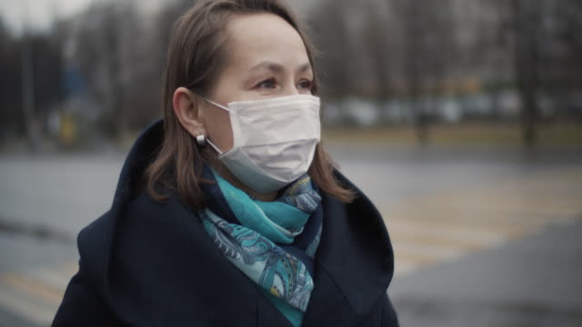 kvinna bär skyddande ansiktsmask på en stadsgata - face mask bildbanksvideor och videomaterial från bakom kulisserna