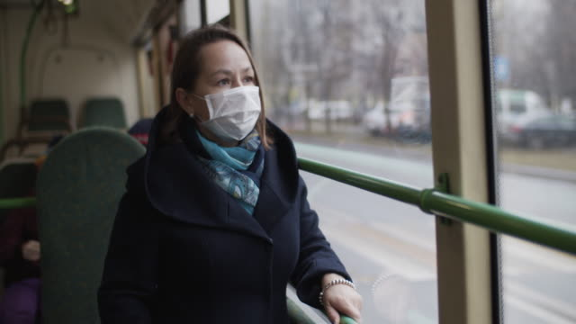 woman wearing protective medical mask in bus - mask filmów i materiałów b-roll
