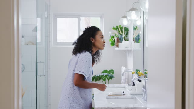 Woman Wearing Pyjamas Standing In Front Of Bathroom Mirror Putting On Make Up Woman wearing pyjamas standing in front of bathroom mirror putting on lip balm - shot in slow motion lip balm stock videos & royalty-free footage