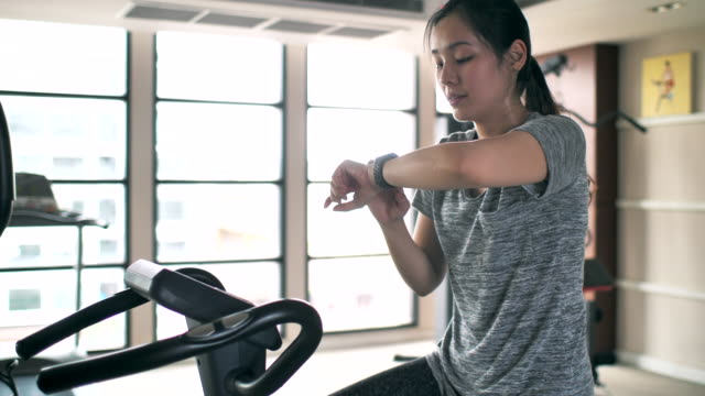 Woman wearing smart watch and using it while exerciseWoman wearing smart watch and using it while exercise