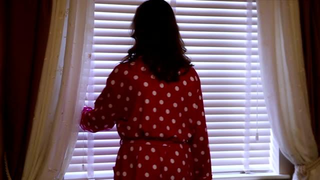 kobieta na sobie szlafrok opatrunek plamisty kitla oknie ślepej próby. - store filmów i materiałów b-roll