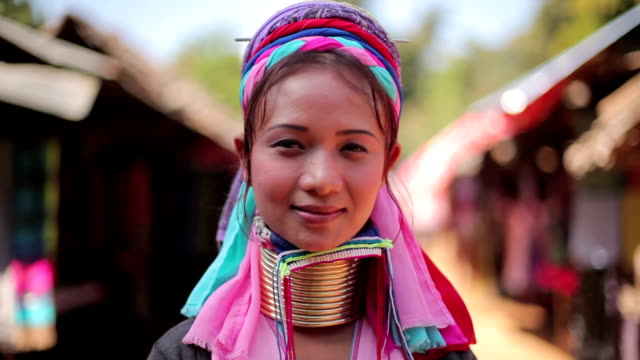 woman wearing the traditional metal rings around her neck,working at a weaving in village video
