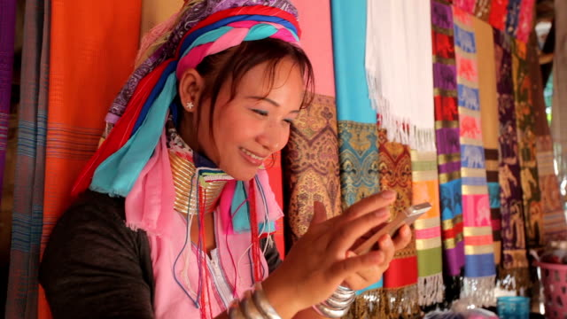 woman wearing the traditional with mobile phone at a weaving in village - этническая группа стоковые видео и кадры b-roll