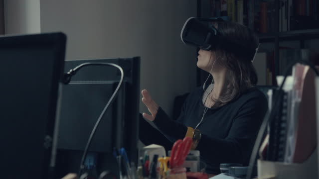 Woman wearing virtual reality headset at office video