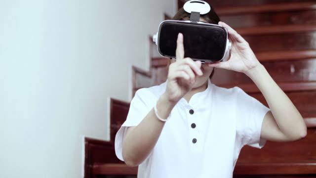 Woman Wearing Virtual Reality Simulator Headset At Home video
