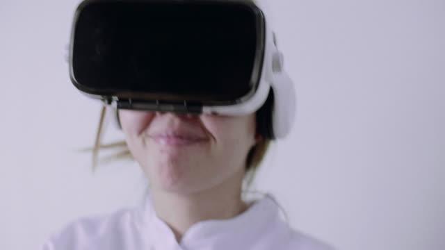 Woman Wearing Virtual Reality Simulator Headset On White Background video