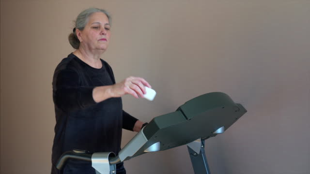 woman wearing wireless headphones, listens music while running on a treadmill. - runner rehab gym video stock e b–roll