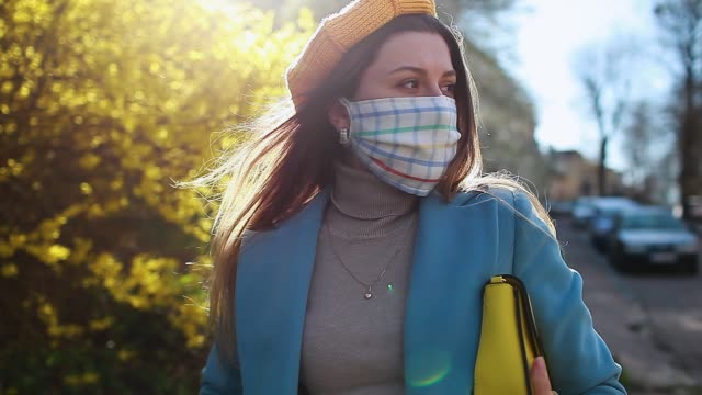 Video Woman wears reusable handmade mask outdoors during coronavirus covid-19 pandemic. Girl walking alone on empty street.