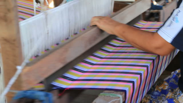 Woman weaving cotton on a loom in Thailand video
