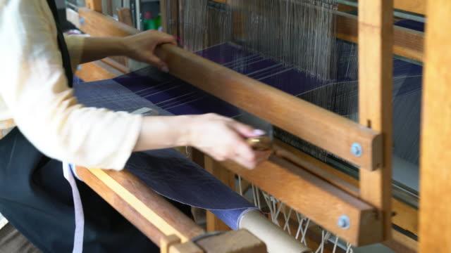 woman weaving fabric, passing the shuttle back and forth - tradycja filmów i materiałów b-roll