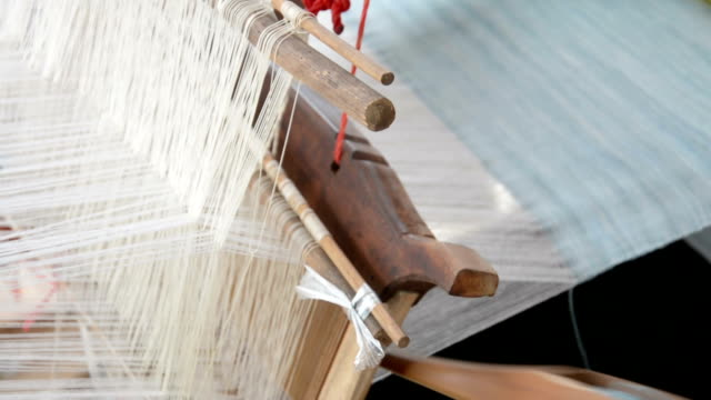 Woman weaving silk in traditional way at manual loom. Thailand video