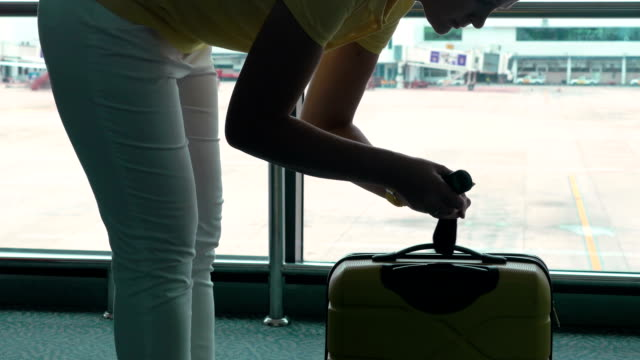 Woman weighs her luggage by compact weigher in airport video