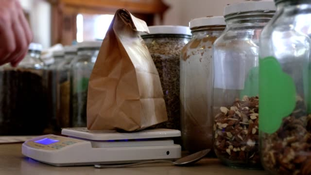 Woman weighs her seeds that she purchased from the sustainable health shop