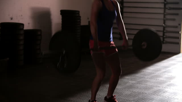 Woman weight training with barbells in a gym video
