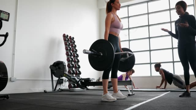 Woman Weightlifting with Personal Trainer Young woman is weightlifting in the gym with her personal trainer. There are two people working out on exercise mats in the background. guidance stock videos & royalty-free footage