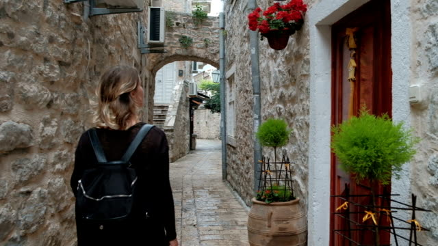 Woman while traveling with interest looks at narrow streets Woman while traveling with interest looks at narrow streets. Fermale back with a backpack walking through the ancient alleys and sees the stone building. guidance stock videos & royalty-free footage