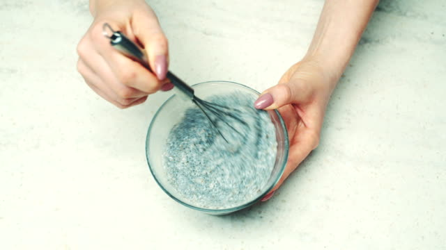 frau schlagen chia pudding zutaten in der schüssel - glutenfrei stock-videos und b-roll-filmmaterial