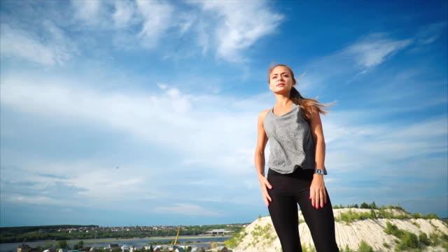 山の上に立つ女性は自然と彼女を吹く風を楽しんでいます - 女性選手点の映像素材/bロール