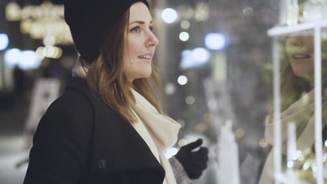 frau schaufensterbummel in den weihnachtsferien - schaufenster stock-videos und b-roll-filmmaterial
