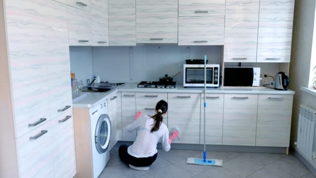 Woman wipes the furniture in the kitchen, timelapse video. video