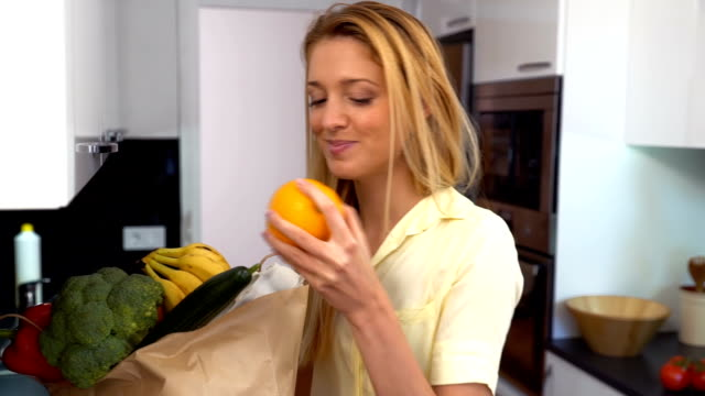 woman with a bag of groceries in the kitchen smiling at the camera. slow motion - stay at home parent stock videos & royalty-free footage