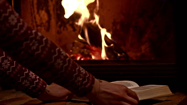 DS Woman with a book by the fireplace Two dolly shots of a woman picking up and putting down an open book on a shelf in front of the fireplace. Also available in 4K resolution. chalet stock videos & royalty-free footage