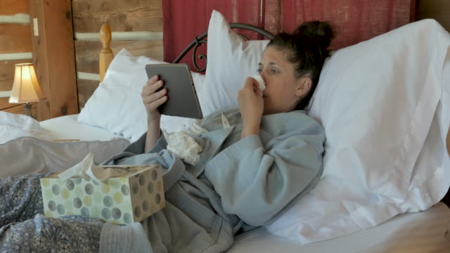 woman with a cough and runny nose video chatting with a tablet in bed - telemedicine stock videos & royalty-free footage