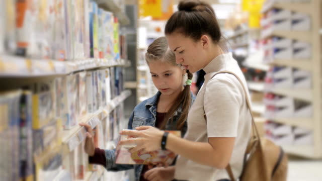 vidéos et rushes de une femme avec une fille dans un supermarché choisit la papeterie pour l'école. achat de fournitures scolaires - fournitures scolaires