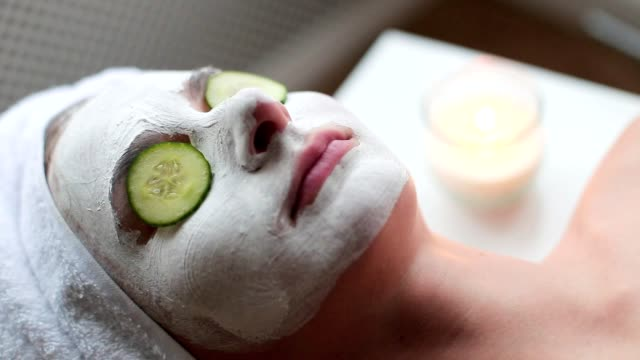 a woman with a facial mask and cucumber on her face - cetriolo video stock e b–roll