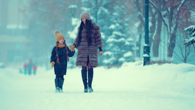 Woman with a girl go under the snowfall. They are having fun. Mom and daughter are walking in the winter.