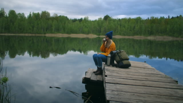 A woman with a hat and a backpack sits on a wooden pier of a forest lake in the mountains and drinks hot drinks tea or coffee from a thermos.