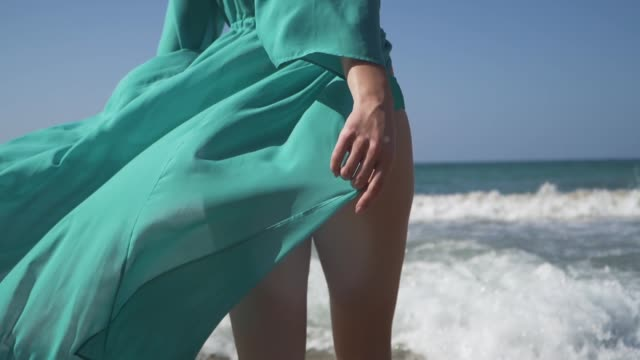 Woman with a perfect body wearing turquoise dress walks into the sea. Dress fluttering in the wind and foaming waves caress beautiful female legs.